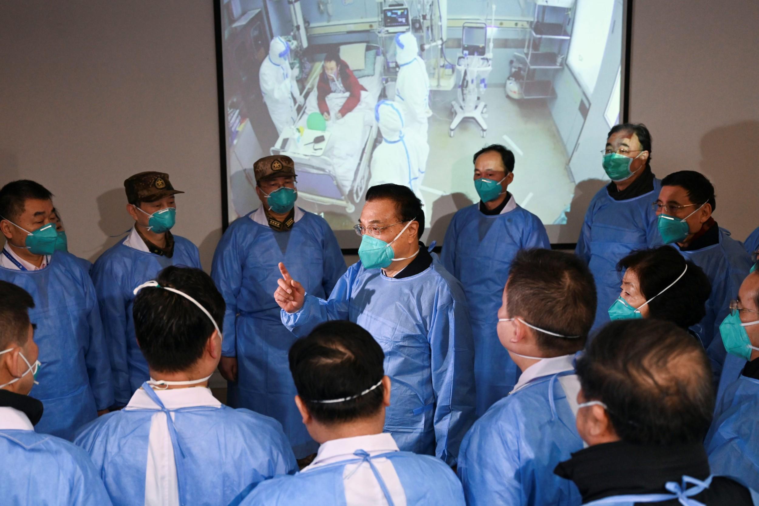 Премијер Кине Ли Кећанг са маском преко уста и у заштитном оделу разговара са медицинским радницима током посете болници у којој су збринути пацијенти са коронавирусом, Вухан, 27. јануар 2020. (Фото: cnsphoto via REUTERS)
