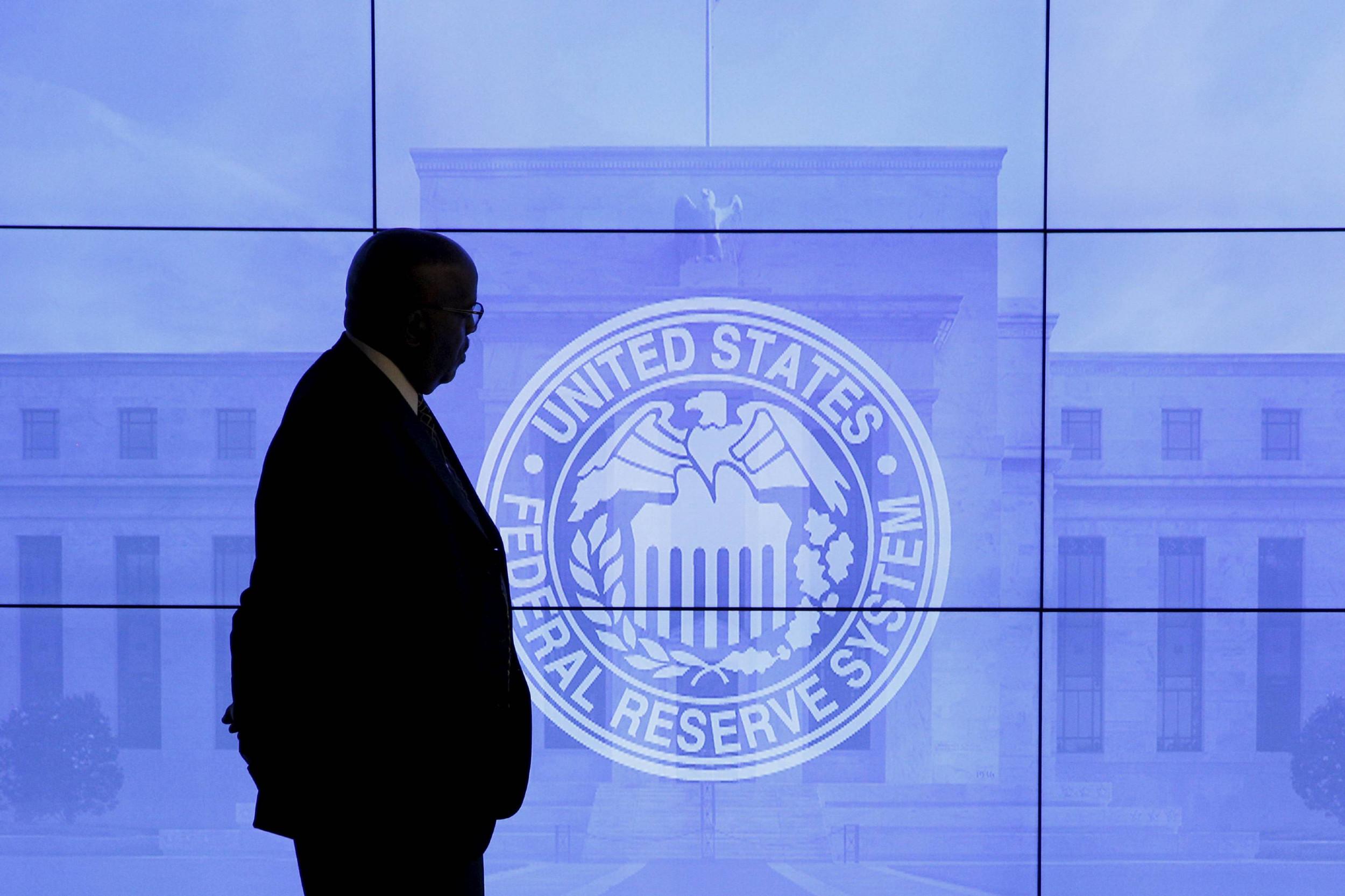 Човек пролази поред екрана на ком се налази грб Федералних резерви (Фото: Reuters/Kevin Lamarque)