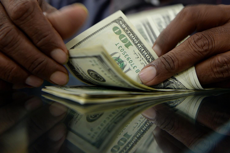 Радник у мењачници пребројава америчке доларе (Фото: Punit Paranjpe/AFP/Getty Images)