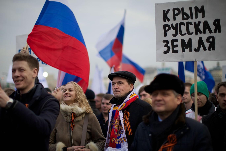 Putinove pristalice na Crvenom trgu sa ruskim zastavama i transparentom na kome piše Krim je ruska zemlja, Moskva, 07. mart 2014. (Foto: AP Photo/Alexander Zemlianichenko)