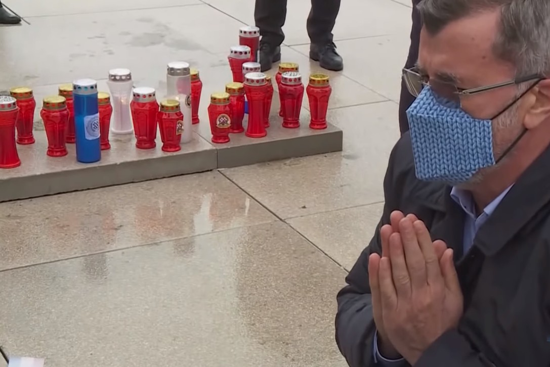 Веран Матић са склопљеним рукама клечи испред споменика у Вуковару (Фото: Снимак екрана/Н1)