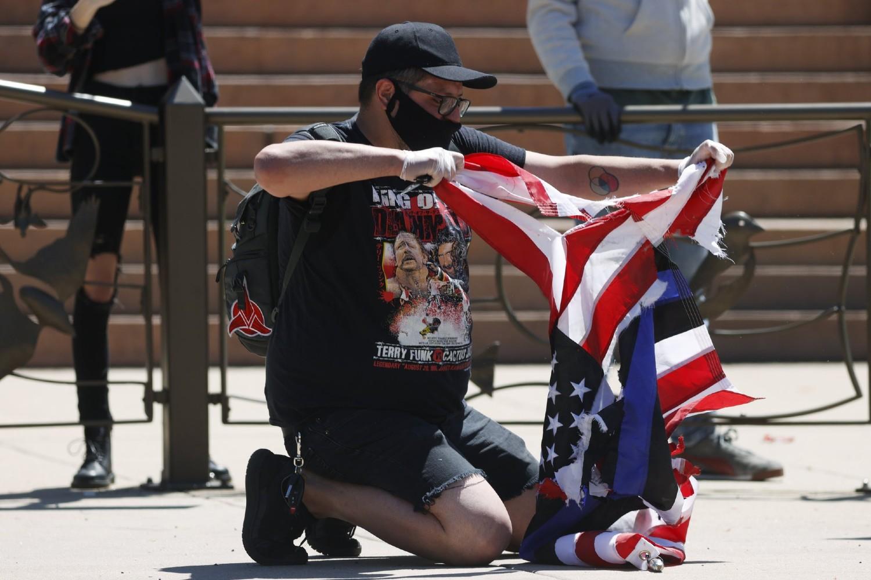 Demonstrant uništava američku zastavu tokom protesta ispred Kapitola zbog ubistva Džordža Flojda, Denver, 29. maj 2020. (Foto: AP Photo/David Zalubowski)