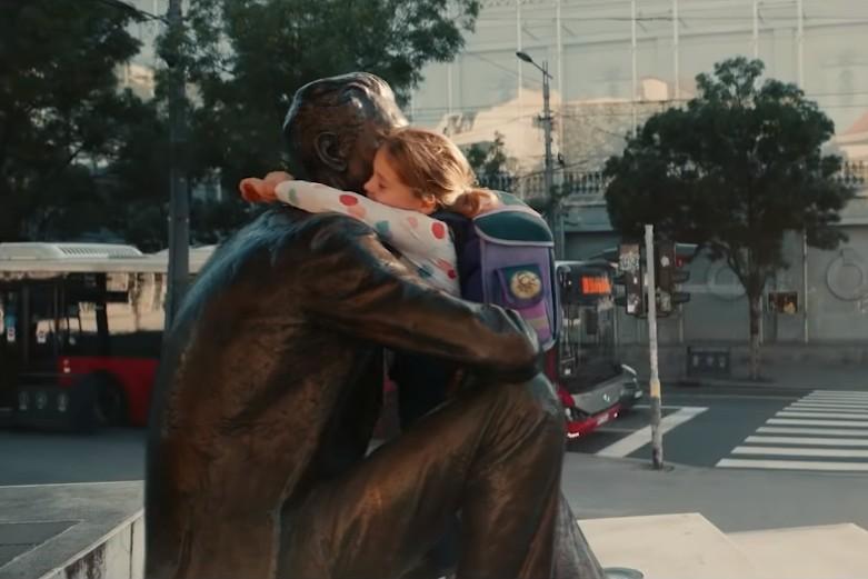 """Сцена у којој девојчица грли статуу Борислава Пекића на Цветном тргу у Београду у склопу рекламе """"Ви сте свет"""" (Фото: Снимак екрана/Ви сте свет)"""