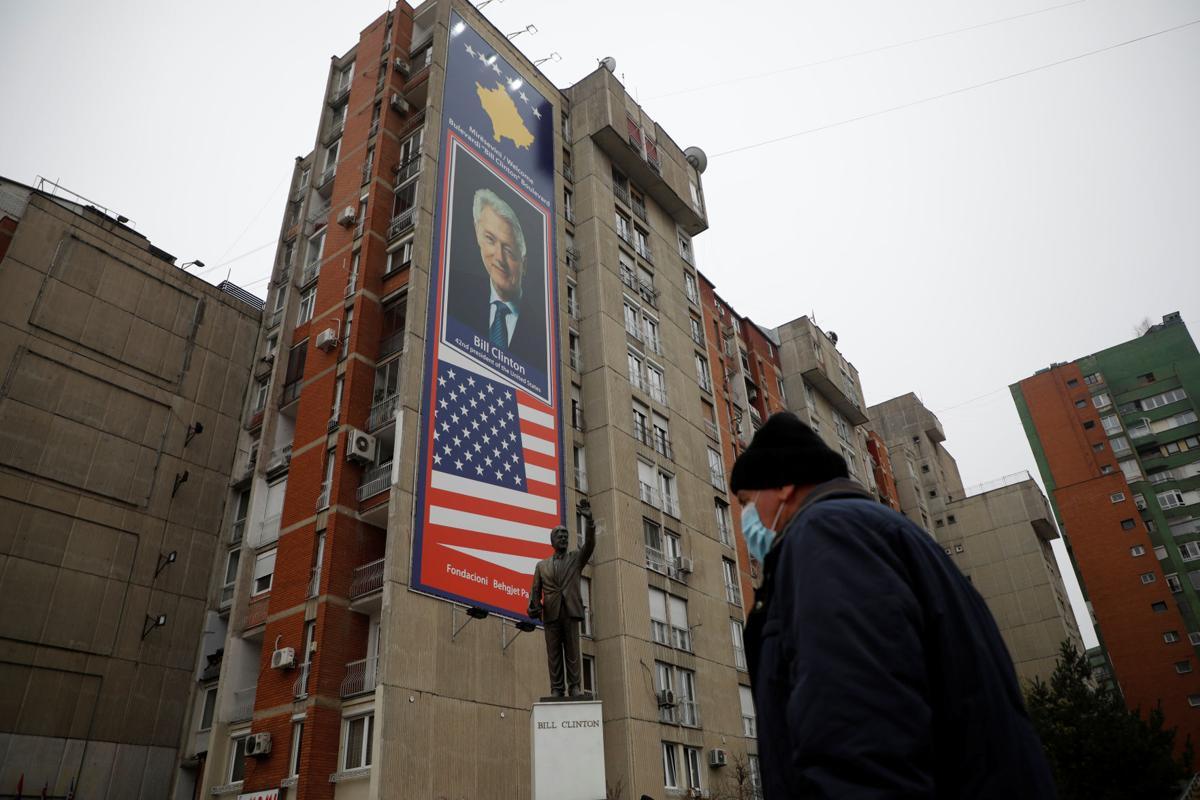 Čovek prolazi pored spomenika bivšem američkom predsedniku Bilu Klintonu, Priština, 20. decembar 2020. (Foto: Reuters/Florion Goga)