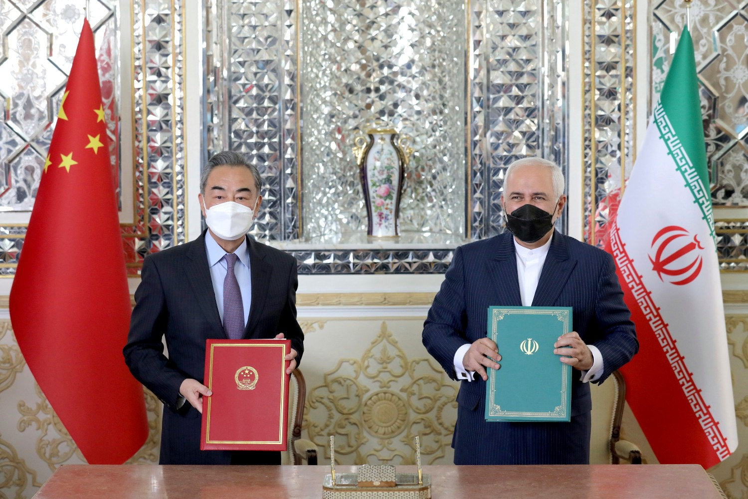 Iranian Foreign Minister Mohammad Javad Zarif (right) and Wang Yi pose after signing a 25-year strategic cooperation agreement in Tehran, Iran on March 27, 2021.AP Photo/Ebrahim Noroozi