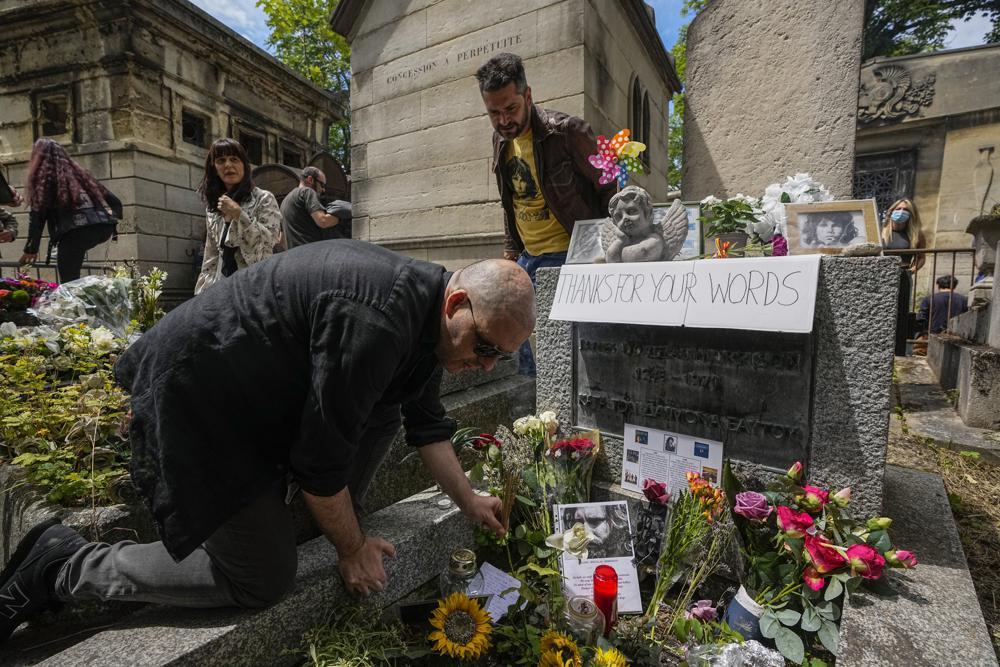 Poštovaoci lika i dela Džima Morisona tokom odavanja počasti na njegovom grobu na groblju Per Lašez, Pariz, 03. jul 2021. (Foto: AP Photo/Michel Euler)