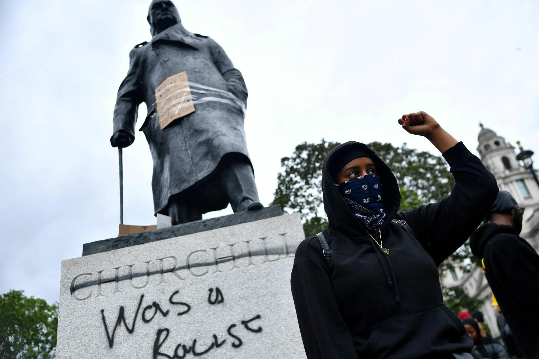 """Demonstrant sa stisnutom pesnicom ispred išaranog spomenika Vinstonu Čerčilu tokom protesta pokreta """"Crni životi su važni"""" zbog ubistva Džordža Flojda, London, 07. jun 2020. (Foto: Reuters/Dylan Martinez)"""