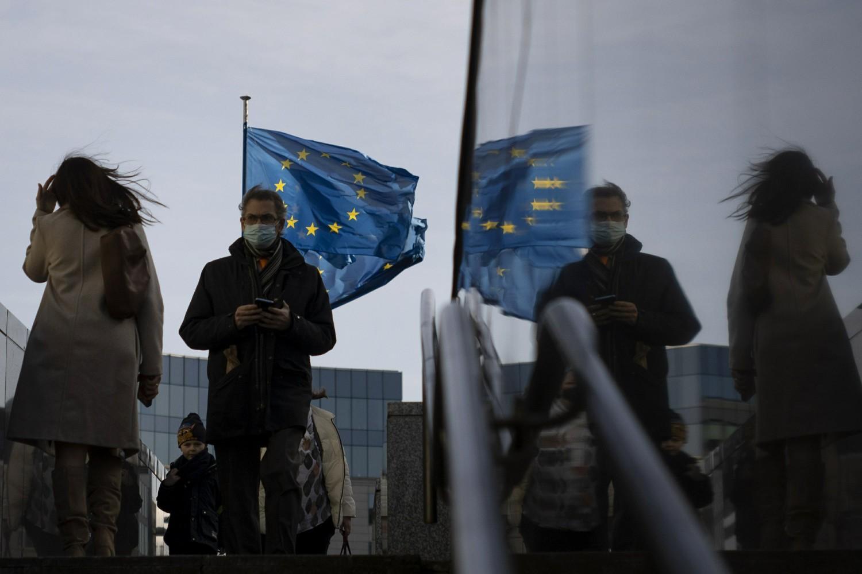Ljudi sa zaštitnim maskama na licu u prolazu pored sedišta Evropske unije, Brisel, 23. februar 2021. (Foto: AP Photo/Virginia Mayo)