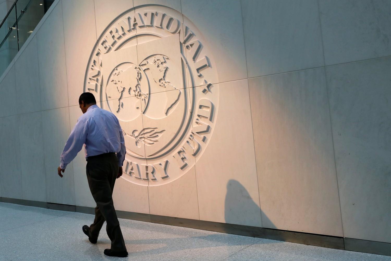 Čovek u prolasku pored velikog loga Međunarodnog monetarnog fonda (MMF) u njegovom sedištu u Vašingtonu, 10. maj 2018. (Foto: Reuters/Yuri Gripas)