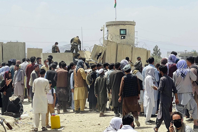 Avganistanci u pokušaju da preskoče zid i domognu se međunarodnog aerodroma Hamid Karzai u Kabulu, 17. avgust 2021. (Foto: AP Photo)