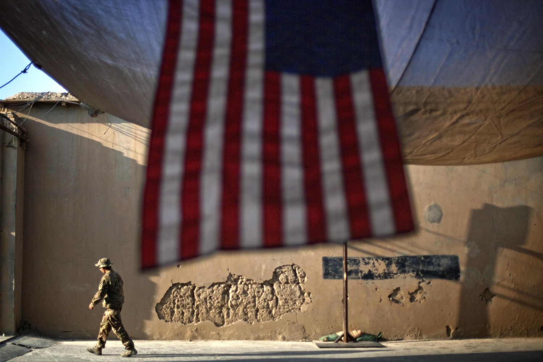 Američki vojnik u prolazu pored američke zastave u jednoj operativnoj bazi u provinciji Kunar (Avganistan), 11. septembar 2011. (Foto: AP Photo/David Goldman)